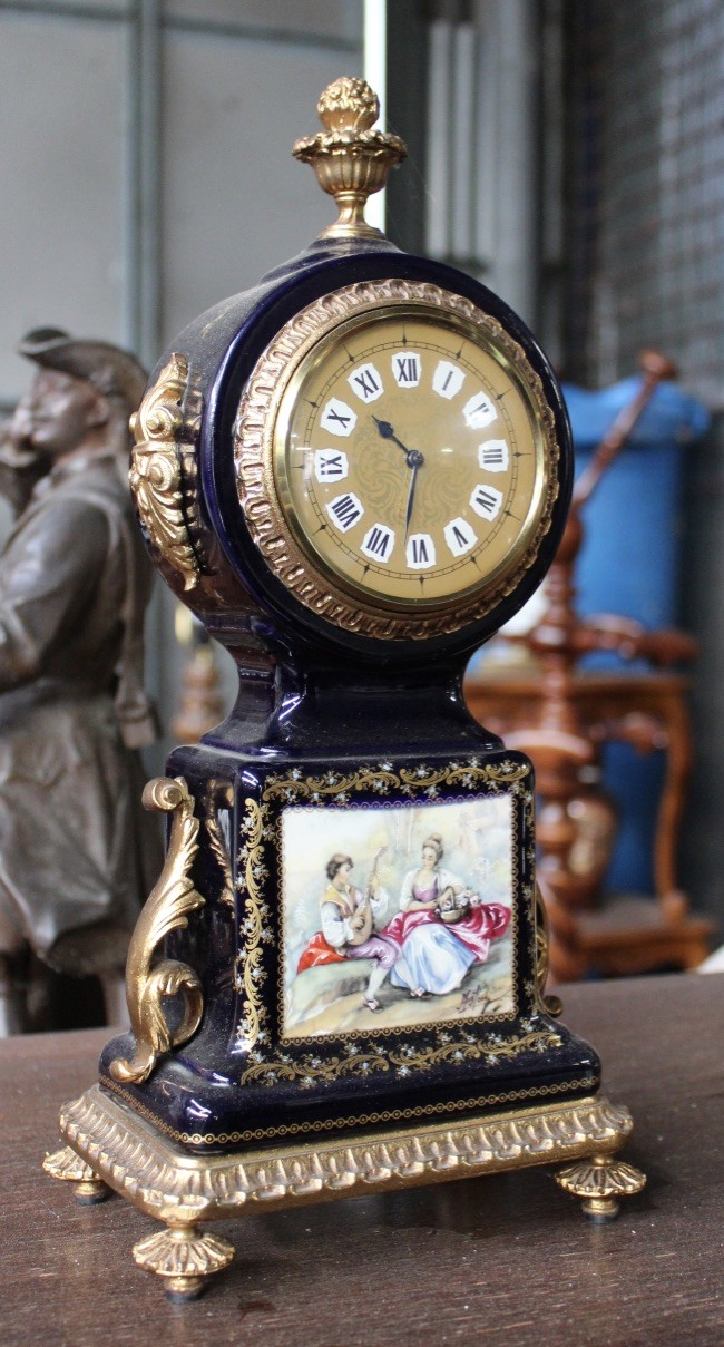 French serves style porcelain and brass mounted mantle clock.