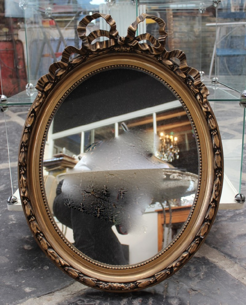 French early 20th century oval gilt and ribbon decorated wall mirror.