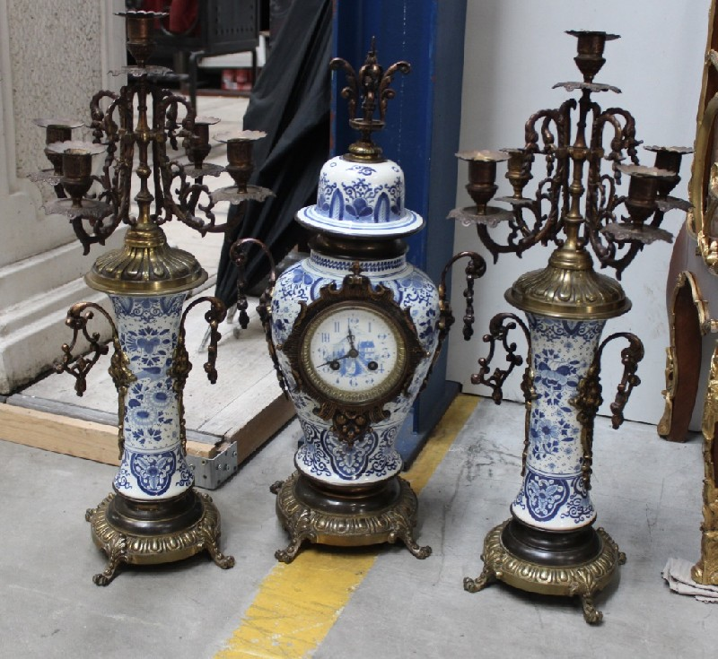 Three piece French late 19th century Delft porcelain and brass clock set. Price $1100