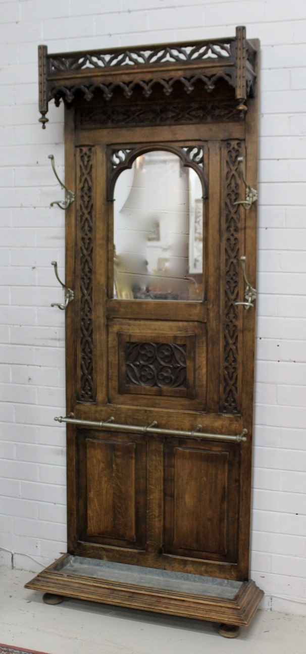 French gothic 19th century carved oak hallstand having brass hooks and mirror back. Price $1350.